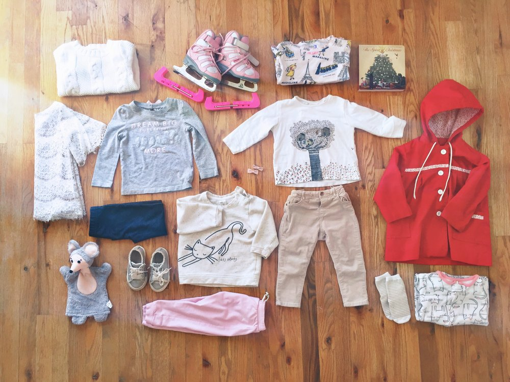 Clockwise from Top Centre:  Toddler Jackson Figure Skates with Guards -  Second Hand,  Madeline Pyjamas -  Really amazing friends at a Baby shower , The Spirit of Christmas -  Indigo , Bird Tree House Shirt -  Zara , Red hooded jacket -  Second hand from my years of toddler life , Kitty Pyjamas -  Carters , Socks -  Carters , Beige Pants -  Carters , Hair Bows -  Carters , Lazy Caturday -  Carters , Pink Joggers -  Zara , Shoes -  Zara , Puppet Mouse -  Mimi & Yeye from Europe , Jeggings -  Carters , Grey Graphic Shirt -  Carters , Lace dress -  Baby Shower gift , Cable Knit Sweater -  Carters