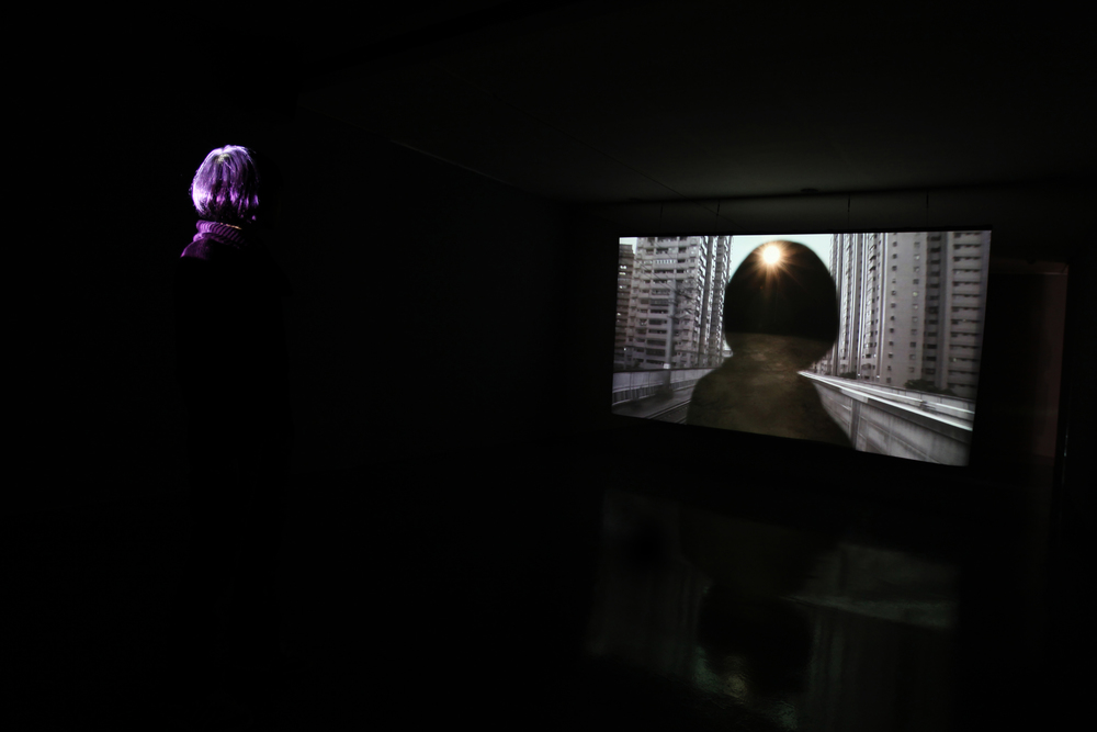 The exhibition scene in Kuandu meseum of Art, Apr 2011 - to see from the left side  The Project <Daily> is initially installed in a dark room. Dual projections are shot onto a translucentscreen that divides the dark room through the center. When the audiences covered one side of theprojection, it will show the image of the other projection : the Taipei city without sun, or the light in theexhibition space.