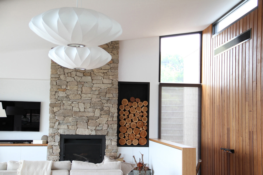 Lounge, living room scene with a stone fireplace, neat logs stacked in alcove to the right, with timber clad wall, and George Nelson pendant lights.