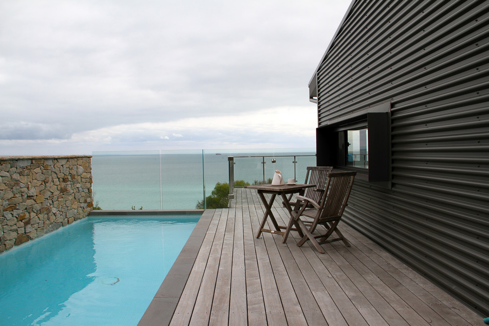 Outside grey timber deck next to a aqua lap pool, overlooking the sea, with a teak table setting for two, next to a colour bond clad wall and inset window.