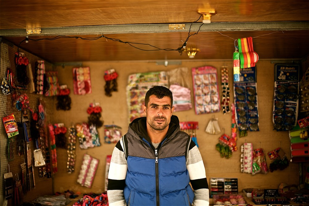 Rahman (name changed) in front of a shop where he works. He says it helps him sustain his family, however, he sees no future for himself in the camp and has decided to go back the first opportunity he has. (photo: Denis Bosnic)