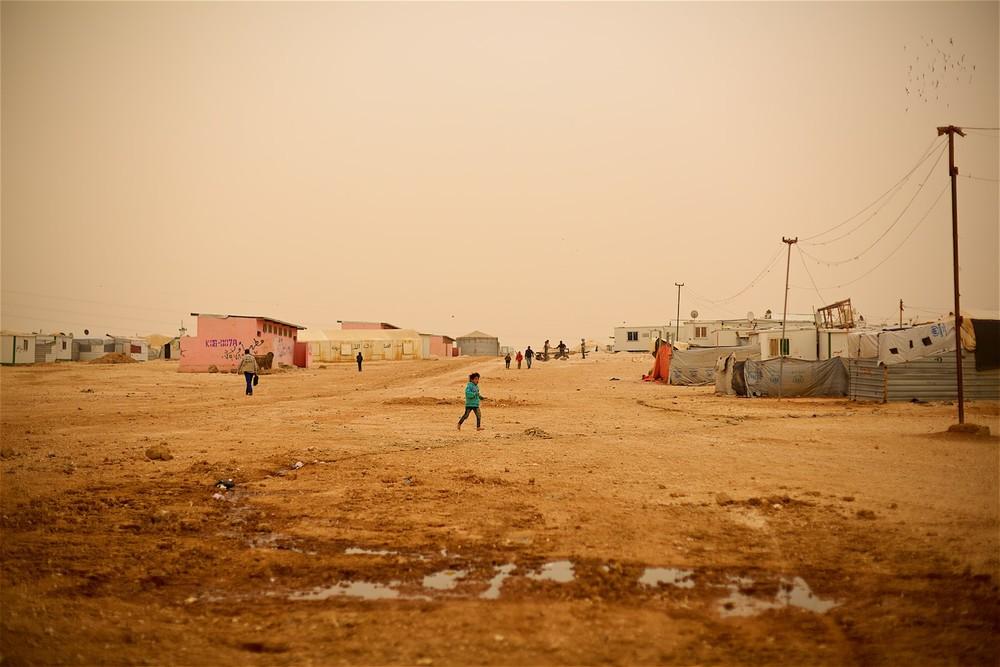 Okrajová štvrť tábora Zaatari. Len niekoľko minút predtým, ako tábor zahalila piesočná búrka. sa bosé deti hrali naháňačku. O niečo neskôr už karavany a stany nebolo vidno.(photo: Denis Bosnič)