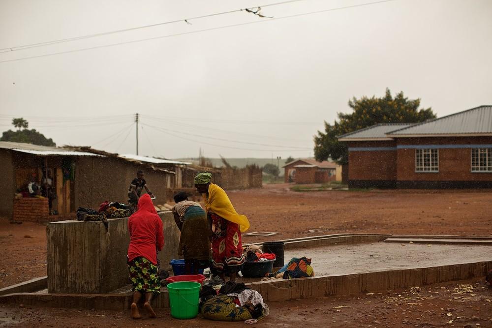 Pitná voda je v táboroch zväčša obrovský problém, s ktorým sa utečenci boria každý deň. Programy UNHCR budujú studne, kvalita vody v nich je však často otázna. Na fotografii utečenci perú prádlo v tábore Dzaleka v Malawi počas dažďa. Keď neprší, rad je dlhý hodiny, keďže na celú štvrť tábora existuje len jedna ručná pumpa zo studne. (photo: Denis Bosnic)