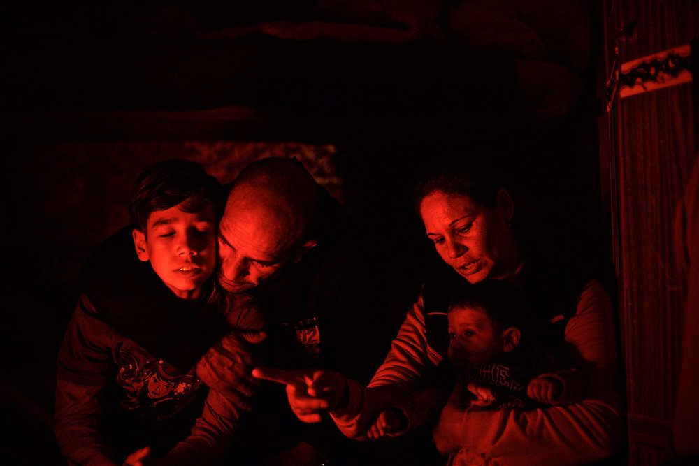 Ramadan, Elena, and their two sons enjoying the heat from an electric heater in their trailer home at the outskirts of Rome. Ramadan is stateless and due to lack of recognition by the authorities, he has been fighting an uphill battle to provide stability for his family. (December 2015) | Photo: Denis Bosnic