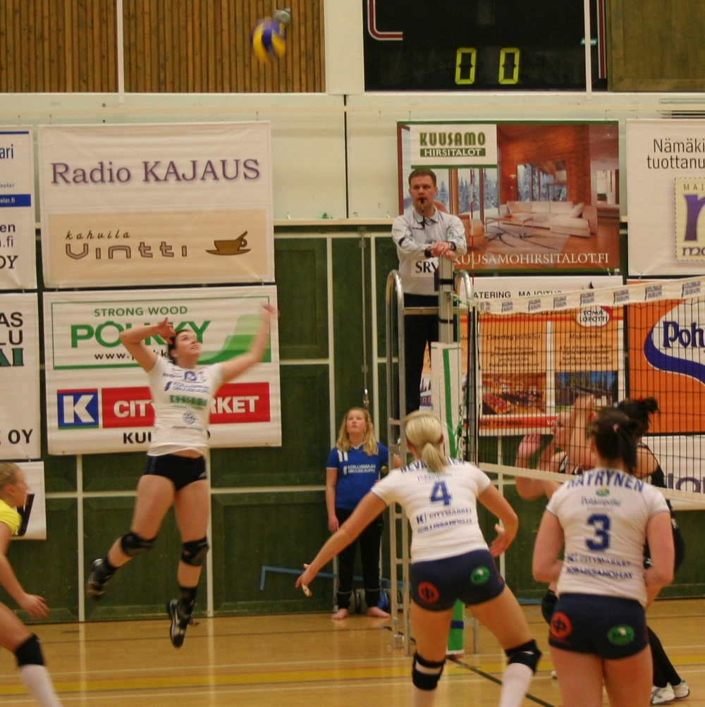 Julianna going up for a kill.  The ball  is the blur at the top of the photo.  Notice that every part of the uniforms have advertising on them.