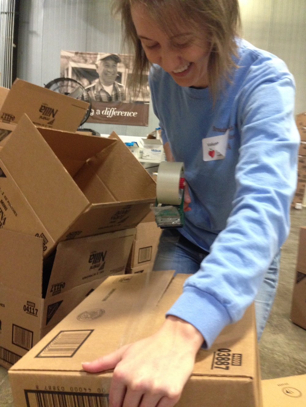 Erin McCoy tapes boxes that will be used for food donations