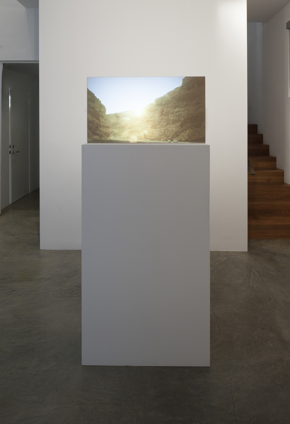 Installation View  (Shulamit Gallery, 2014)   Prodigal Sun,   2012  Single Channel HD Video Projection onto Glass in Pedestal, No Sound, TRT 2:20, Looping 69 x 30 x 12 Inches (Pedestal and Glass)