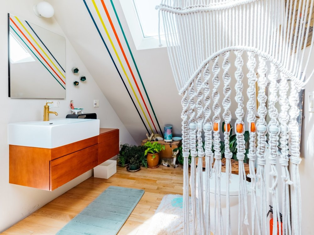 Windy's bathroom upstairs showcases the same stripes, as well as an array of plants and a porcelain deer nestled in the foliage. (Sothear Nuon)
