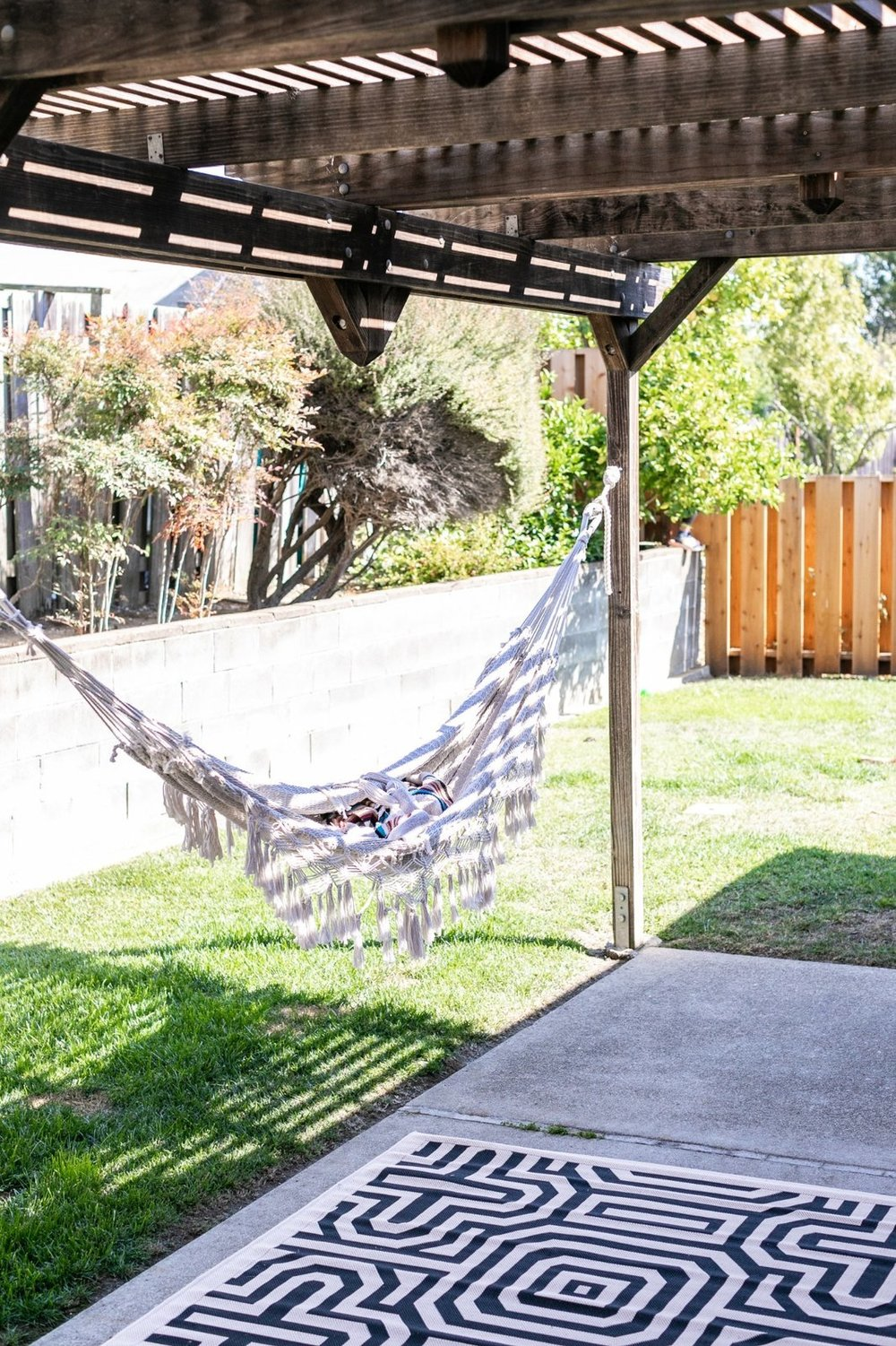 On warm days, Encarnacion can be found lounging in her hammock in the backyard. (Sothear Nuon)