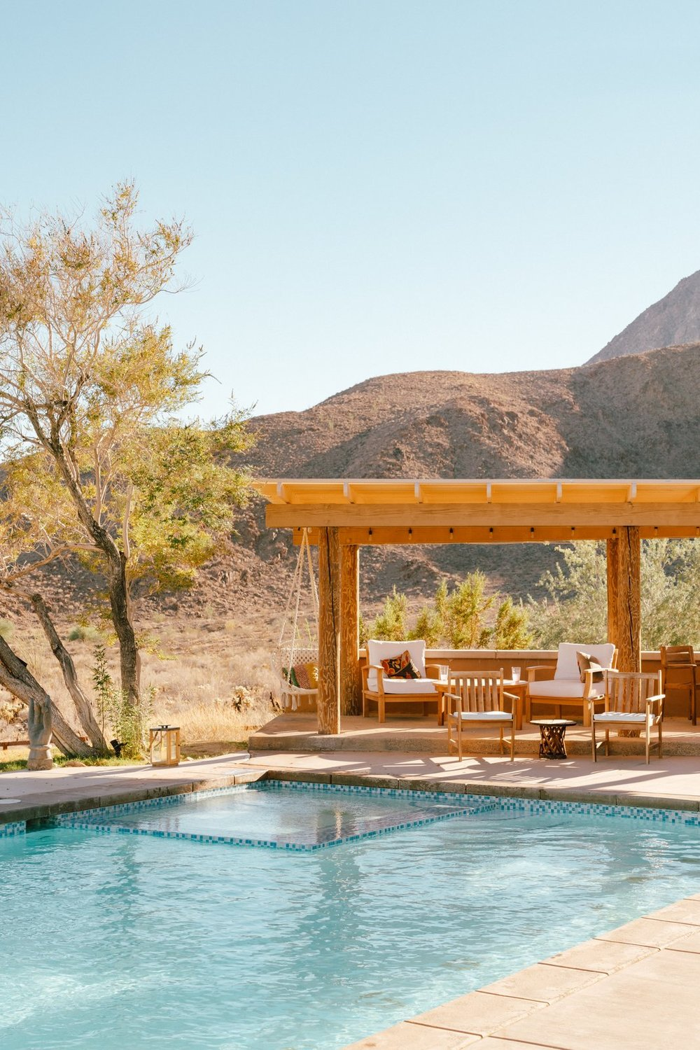 Despite the home's stylish interiors, Young is most drawn to what lies outdoors—a lounge for quiet moments and al fresco dining, a pool, an outdoor shower, the views, a 1972 VW Meyers Manx dune buggy, and a raised adobe platform with a teepee on the back veranda. (Tim Melideo)