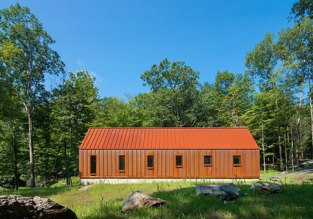The Pond House has a standing-seam roof and wall panels made of Cor-Ten steel that throw the forest around it into relief. (Bjorg Magnea)