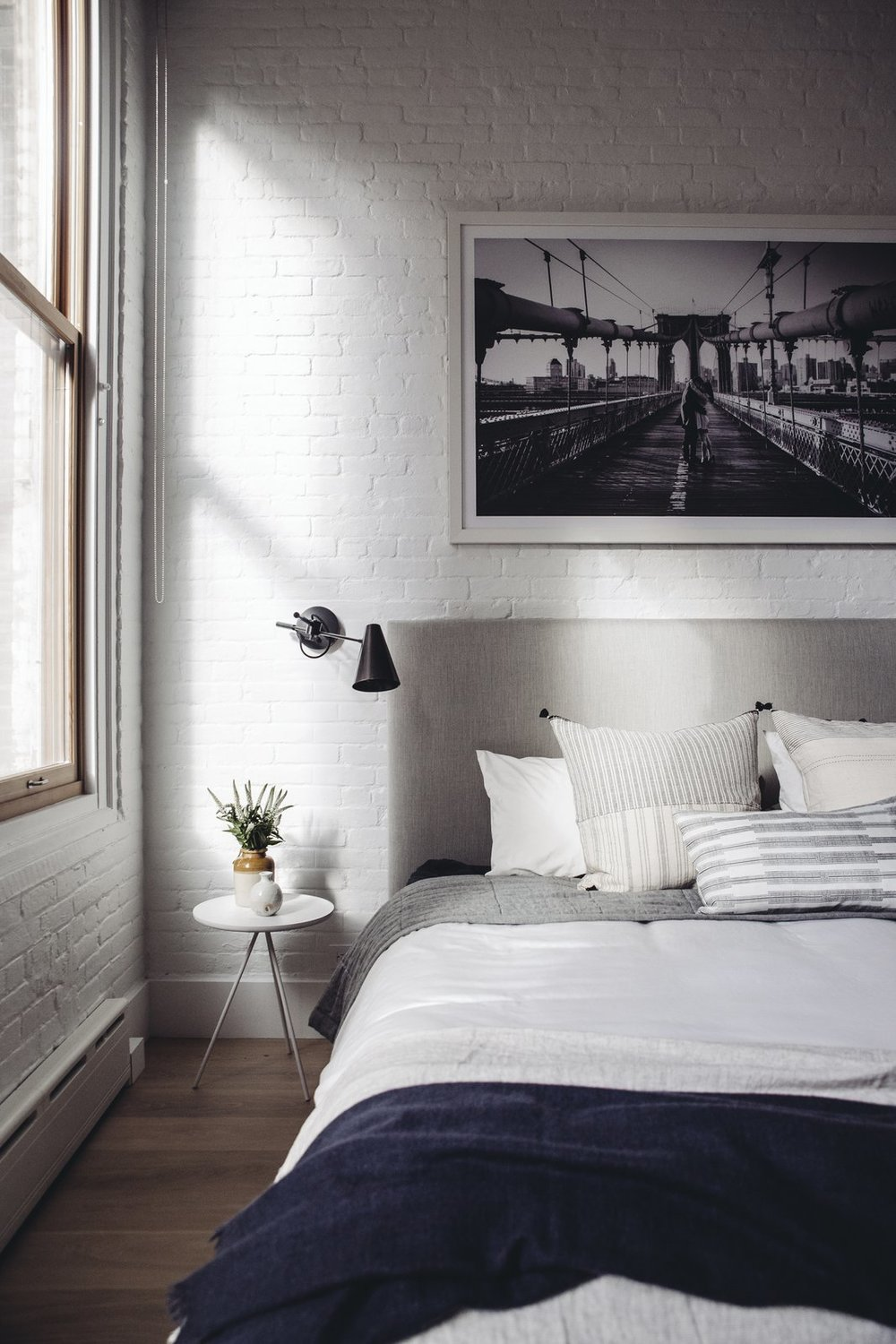 Exposed brick and natural light add a touch of quintessential New York loft style to the updated home. Restoration Hardware sconces, pillows from Injiri and Susan Connor, and a throw from ABC home tie the room together in the perfect combination of structured and cozy. (Chloe Leroux)