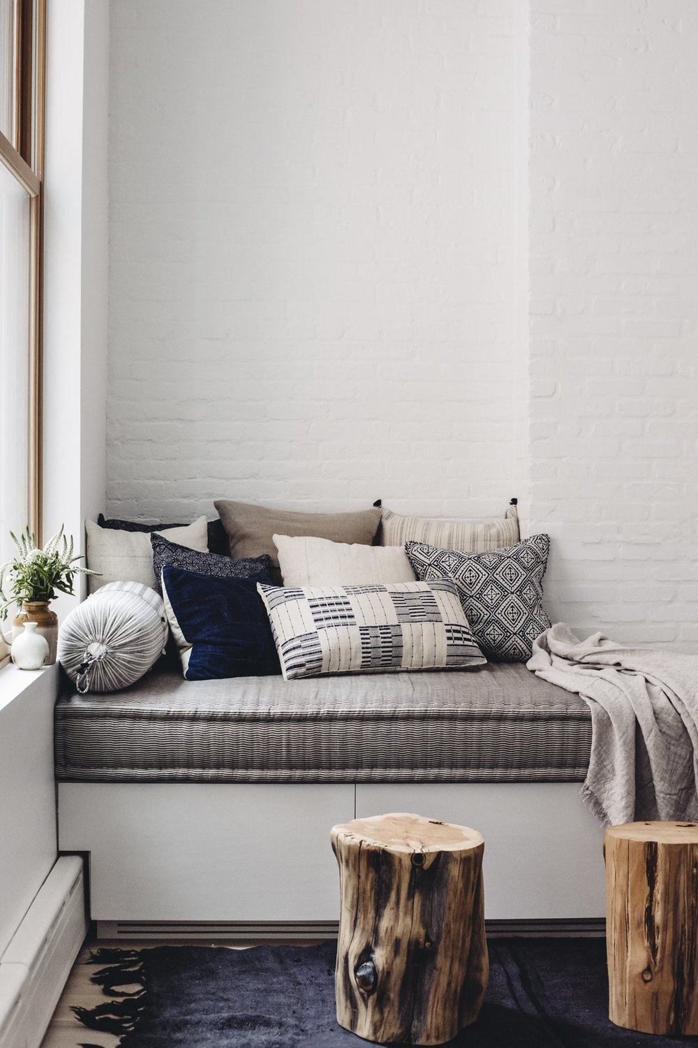 The built-in day bed by JFL Custom Builders provides a cozy corner. Topped with a pillow assortment by Walter G textiles, Bungalow Decor, and Injiri, it's ideal for cuddling up with a book and a blanket. West Elm wood stumps and an antique hemp rug round out the space with some added depth. (Chloe Leroux)