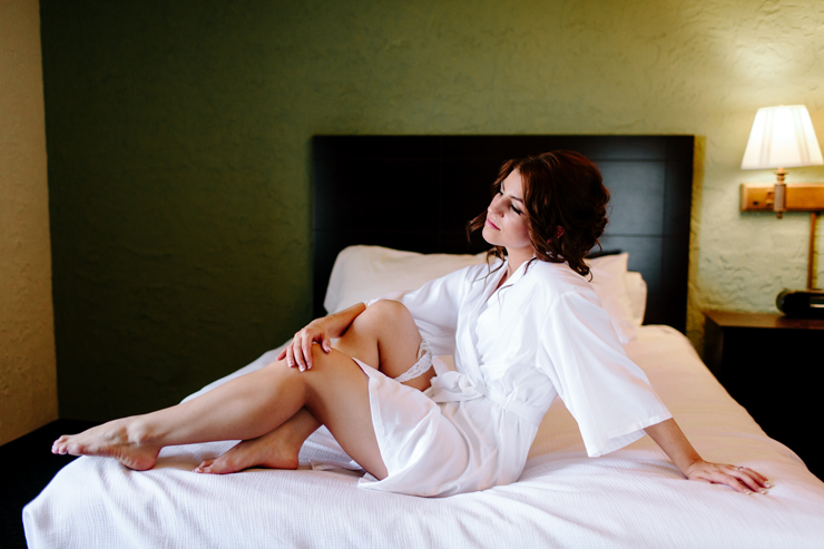 Bride posing on a bed at a hotel in bloomington, illinois on her wedding day