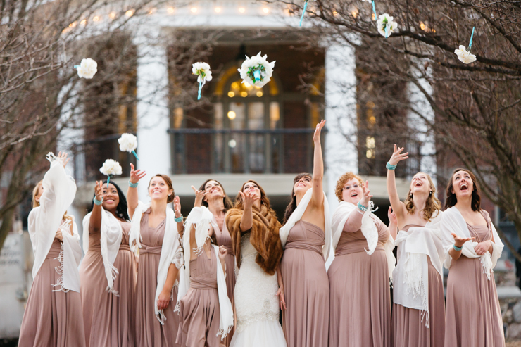 Bridesmaids throwing flowers wearing pink long gowns