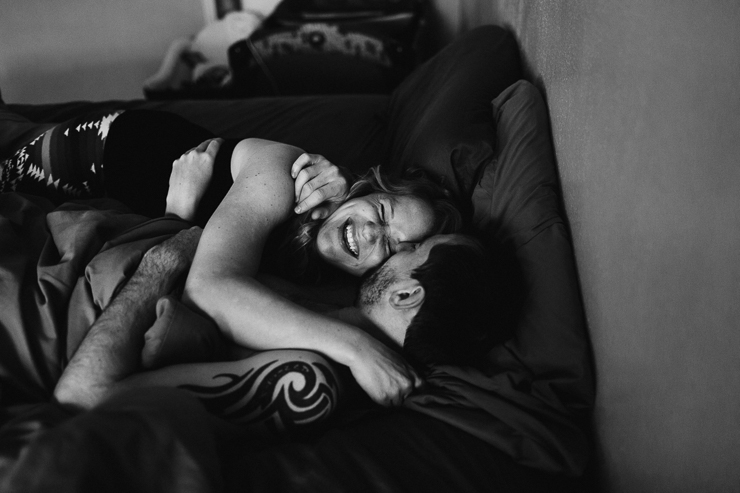 Lifestyle photography of man and woman snuggling in bed