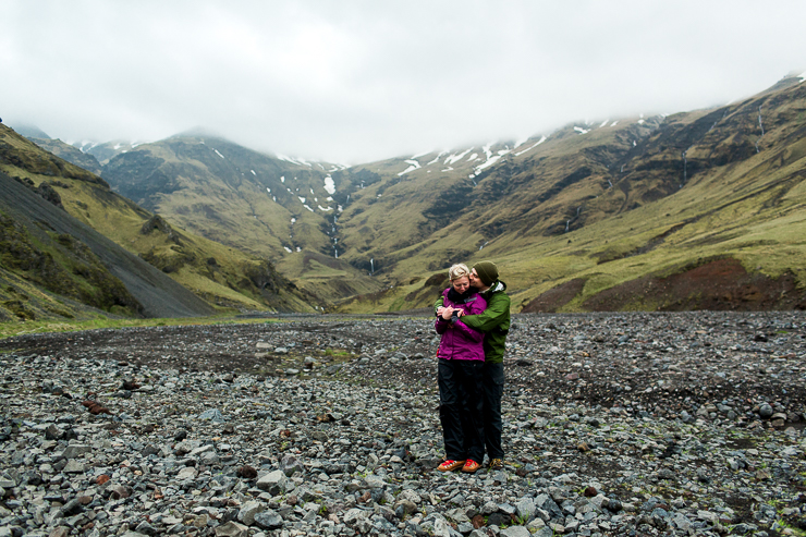 couple standing in the mountains in Iceland on the way to Seljavallalaug