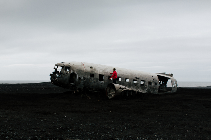 Man standing on the US Navy DC3 Wreckage at Solheimasandur, Iceland