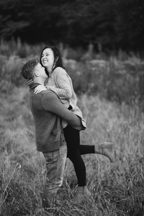 Engagement photos of man picking up girl in field