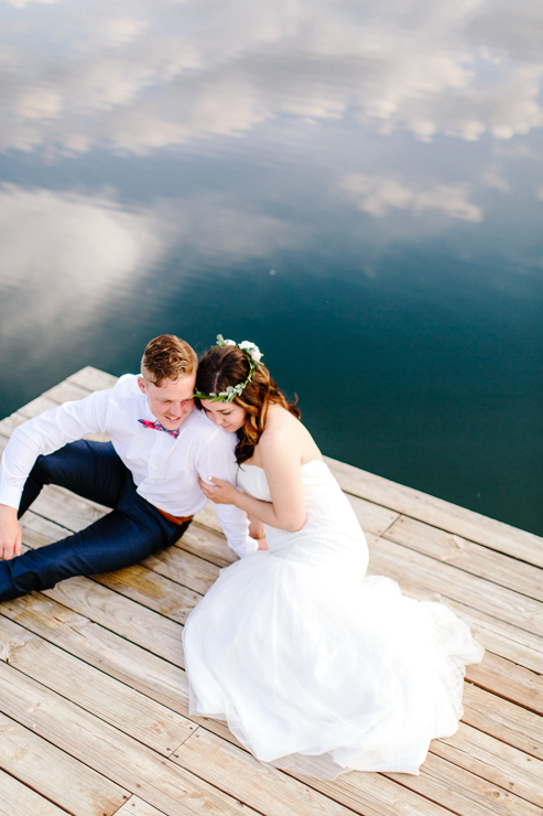 Bride and Groom Portraits sitting on a dock by the lake at a childhood home
