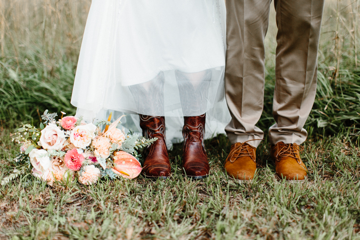Bride and Groom's shoes with cowboy boots and stunning florals by Splendor Of Eden