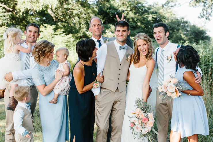 Fun family photo with bride and groom outdoor on family farm