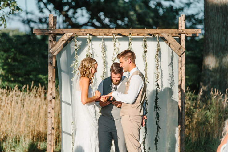 Bride and Groom giving one another rings during outdoor wedding ceremony on grandparents' farm