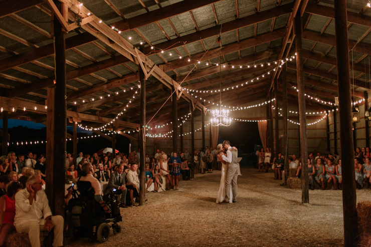 Wedding Reception at Grandparents' family farm and barn decorated with hay bales, quilts, chandeliers, and edison bulbs