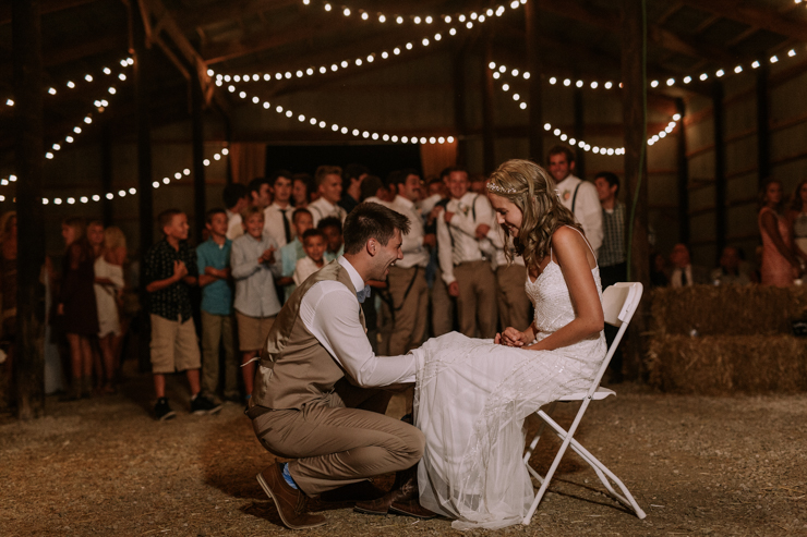 Garter toss at midwest barn reception lit with edison bulbs