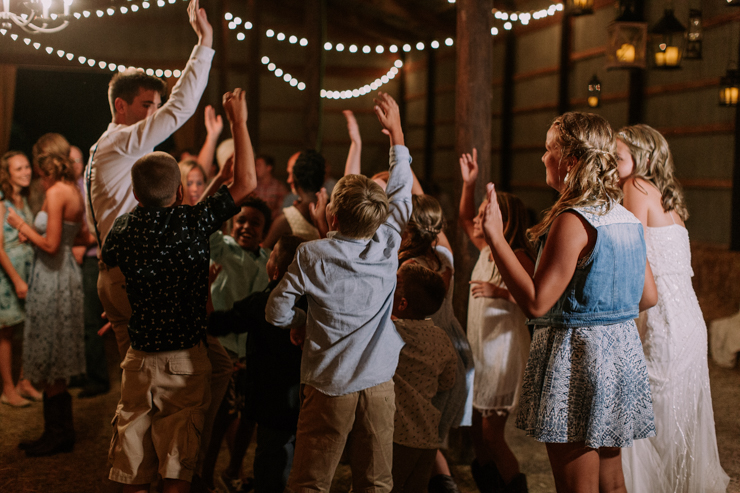 Bride, groom, and friends dancing at midwest barn reception lit with edison bulbs