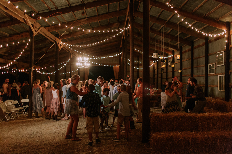Bride, groom, and friends dancing at midwest barn reception lit with edison bulbsBride, groom, and friends dancing at midwest barn reception lit with edison bulbs