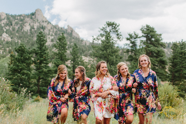 Bridesmaids in floral robes standing in front of the mountains in Estes Park on wedding day