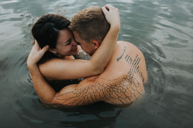 Intimate photography of a married couple in the water together partially nude