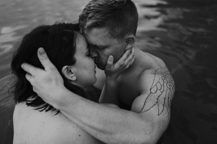 Intimate photography of a married couple with amazing tattoos in the water together partially nude