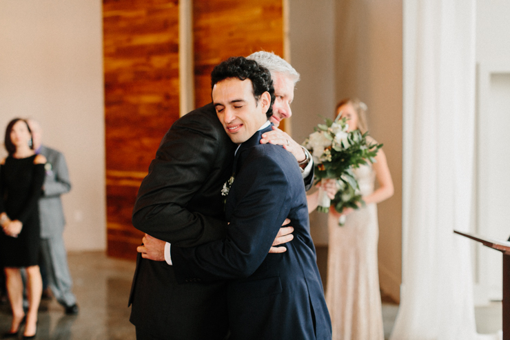 Father hugging groom at wedding