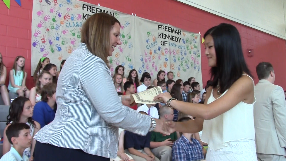 Principal Lisa Altham-Hickey congratulates a student with a handshake and certificate.