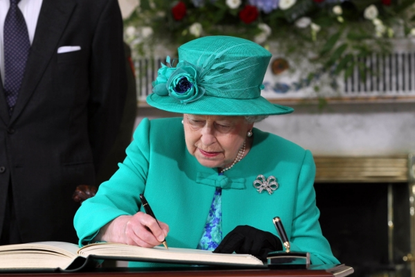 Her Majesty Queen Elizabeth II as she signs the visitors book in Aras An Uachtarain while on the first day of her State Visit to Ireland.