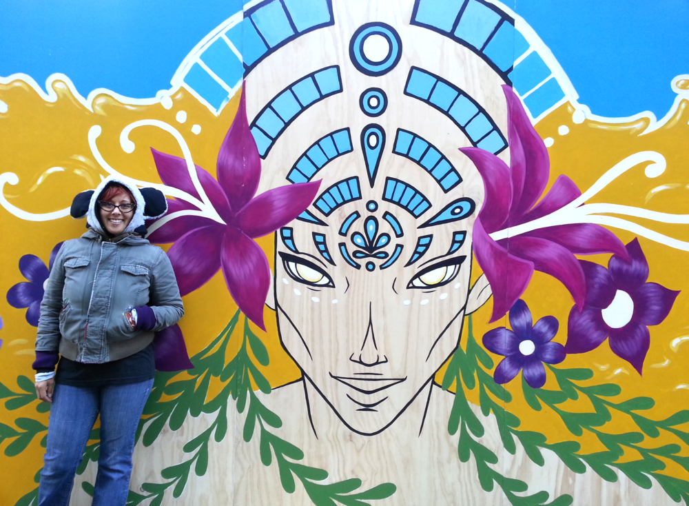 Artist Jenn Brisson in front of the mural at Hastings and Granville.