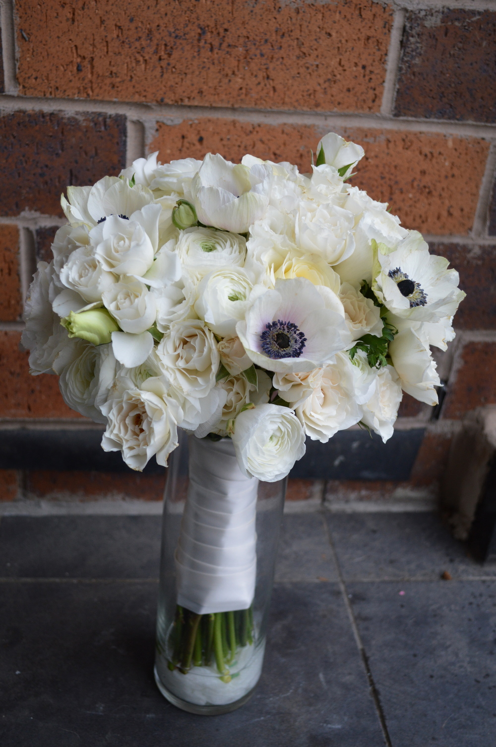 White Ranunculus, French Anemones, white Spray Roses and white Lisianthus wrapped in an Antique White ribbon and accenting pearl pins.