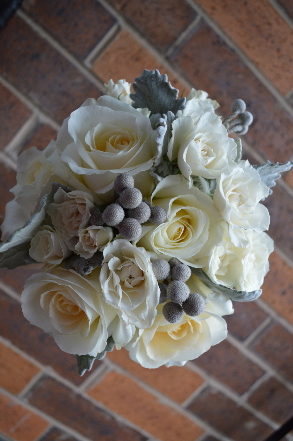 Bridesmaids had matching bouquets of Blizzard Roses, Spray Roses, Brunia and accenting Dusty Miller, wrapped in a silver ribbon with accenting pearl pins.