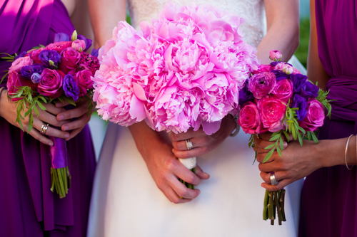 "An abundance of pink Peonies were used for the Bridal Bouquet. Both Bridesmaids had a mix of: ""Cherry Oh"" Roses, deep pink Ranunculus, deep purple Lisianthus and Marigold foliage."