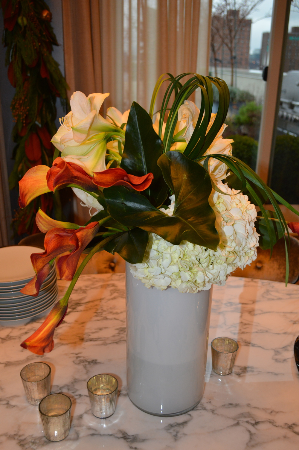 Beautiful mango Calla Lilies, white Hydrangeas and Amaryllis with accenting foliage and lily grasses in tall over sized white glass vase.