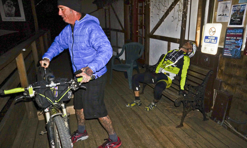 Eddie O'Dea, exhausted after 400 miles, as Kevin Hinton helps set his bike aside. Don't idle, Eddie. (c) Josh Spice 2013