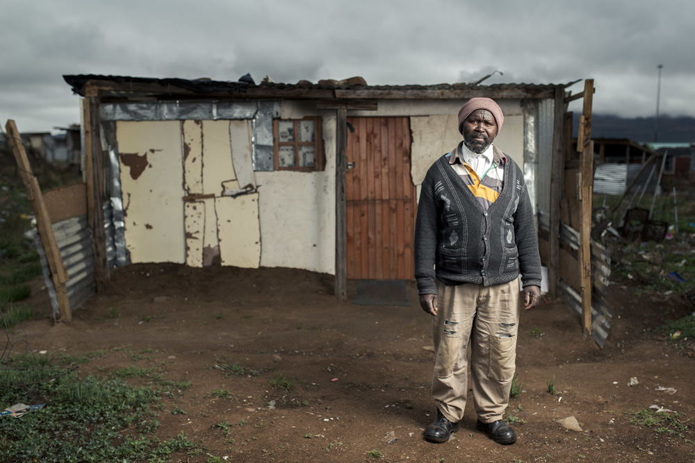 Mthuthuzeli Mtshange infront of his shack on the outskirts of Queenstown, Eastern Cape.