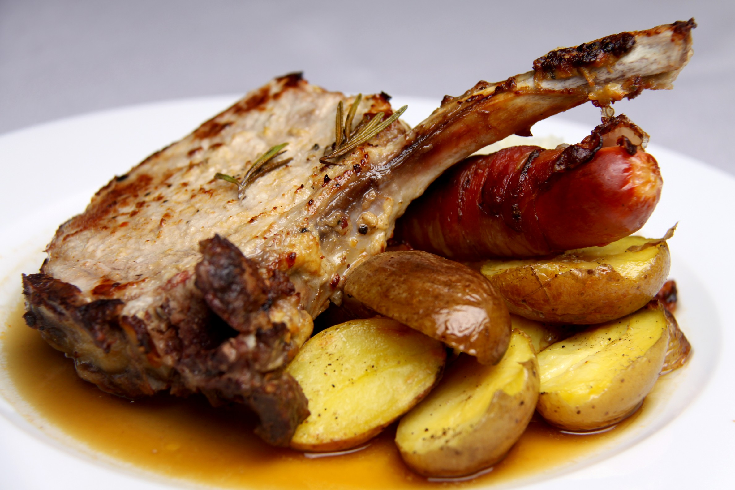 Pork chop with sour cabbage and sausage in bacon coat