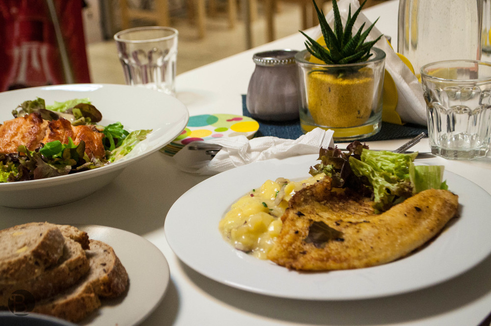 Napravo je tilapia so zemiakovým šalátom, vľavo lososový šalát.
