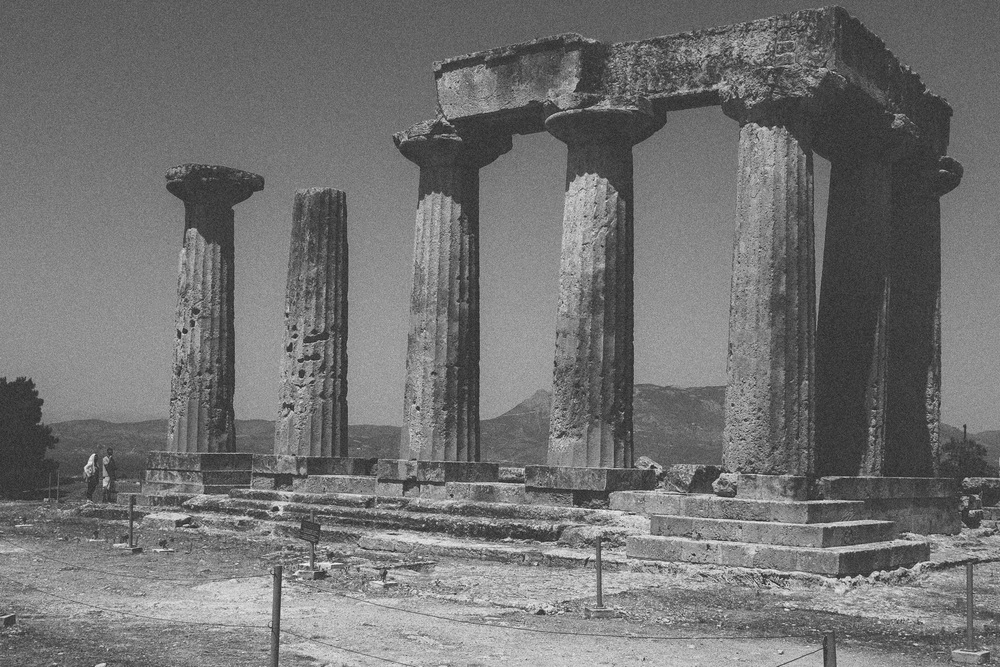 Photo 23. Ruins of another temple dedicated to the God Apollo with two people at left illustrating the scale.  Corinth, Greece, 2014.