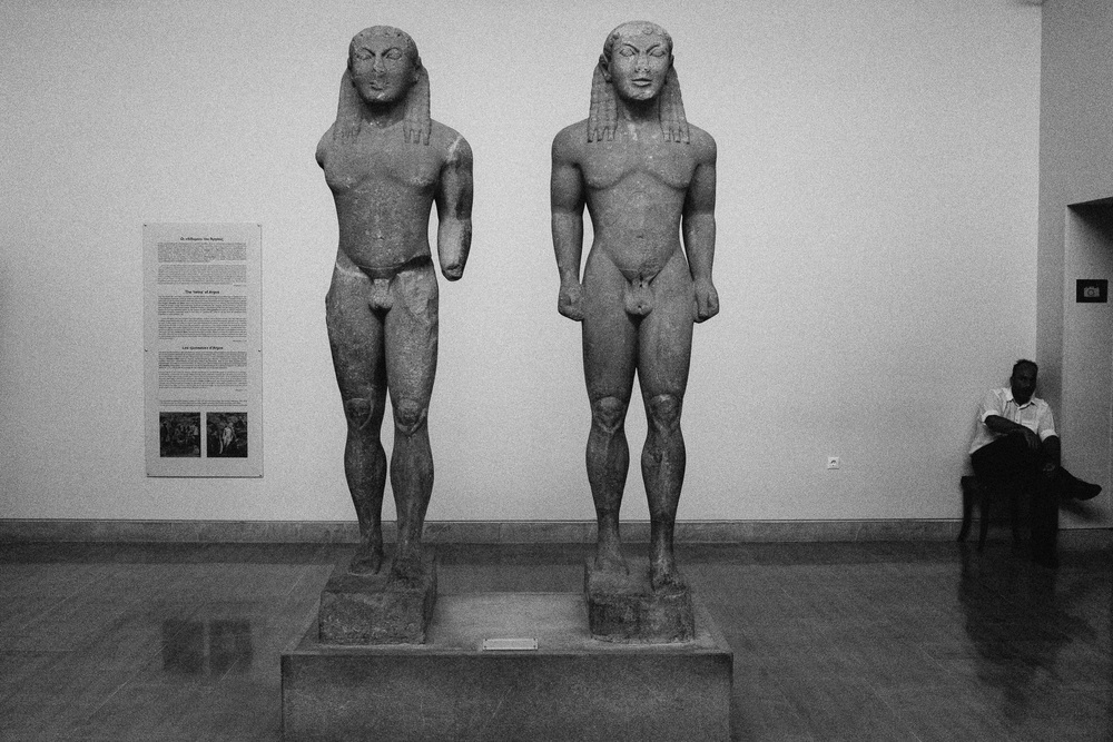 Photo 61. Two archaic period Kouros - characterized by the left foot forward, and hands at the side.  Kouros were male representations of the ideal of youth, and used as tributes to the Gods in the archaic period (800 - 480 BC).    Olympia, Greece, 2014.