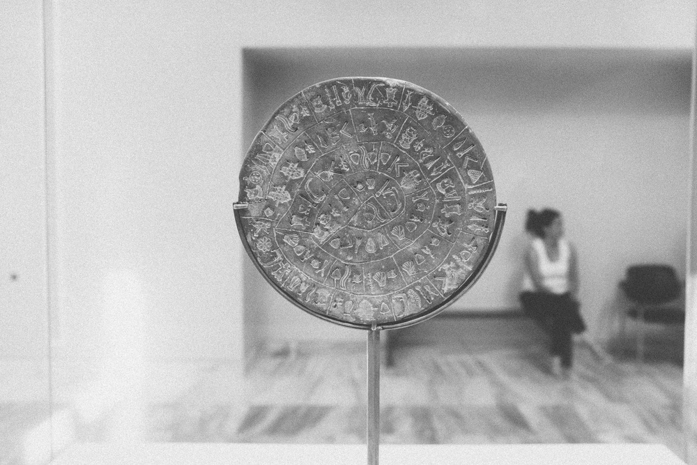 Photo 26.  The Minoan Phaistos Disc is a precursor to the Greek alphabet but has yet to be interpreted (1850-1600 BC).   Heraklion Archaeological Museum, Crete, 2014.