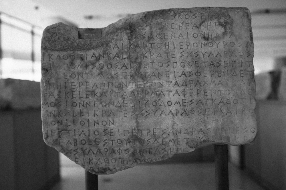 Photo 28.  A Greek stele shows the written form of ancient greek language .   Derived from an ancient phoenician alphabet it was the first to use letters for both vowels and consonants.   Acropolis Museum, Athens, 2014.